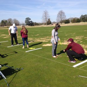 Mississippi State Assistant Golf Professionals, Ryan Wilhelm and Trey Adams demonstrating how to hit a golf ball.